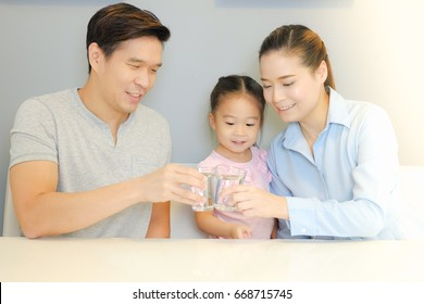 Asian family drinking water with together