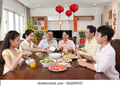 Asian family eating at big table for New Year celebration; couplets with best wishes for coming year in the background