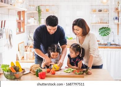 アジアの家族は家庭で台所で料理や遊びを楽しむ