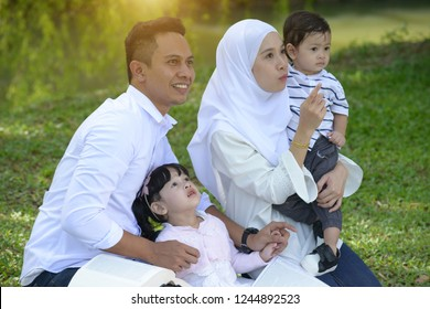 asian family enjoying quality time with father, mother,son and daughter in park