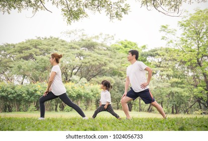 Asian family exercising and jogging together at the park. Group of asian father mother and daughter stretching after sport. Sport healthcare medical spring summer together family's day concept.