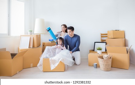 Asian family father mother daughter packing cardboard box move to new house, online marketing e-commerce unpack stuff belongings home delivery. Lifestyle happy asian family together relocation concept