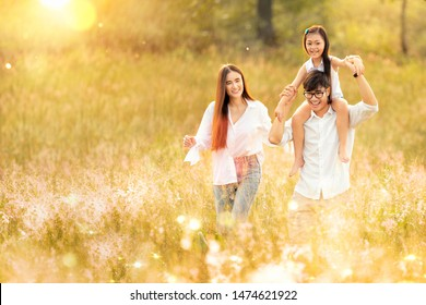 Asian family father, mother and daughter play togather in the outdoor park with sunrise and goldent colour, this image can use for family, relax, freedon, summer and travel concept