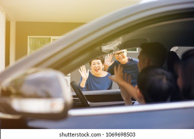 Asian family of father, mother and son waving goodbye to grandfather and grandmother as they take off their journey