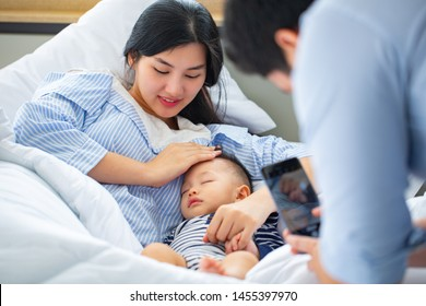 Asian familyfather using smartphone for take photo mother and sonat room.