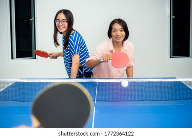 Asian family fun playing table tennis or Ping pong indoor together leisure with competing in sports games in the house. Mother and daughter enjoy recreation or exercise stay at home in Thailand