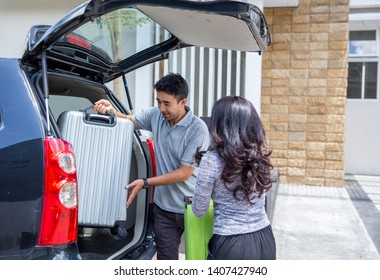 asian family get ready to holiday celebration vacation. bringing suitcase to trunk of the car balik kampung concept