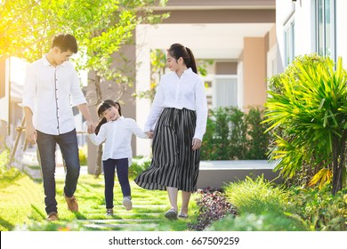 Asian family are going out of the house , Parents and children were walking hand in hand together a happy in garden.