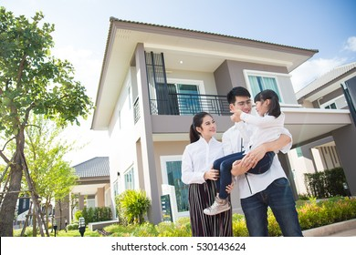 Asian family Happy Daughter pointing parents to look after her , with child over house background.