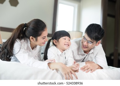 Asian family  happy Parents and children in bed at home