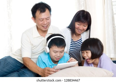 Asian family having fun with tablet computer