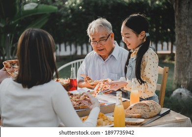 Asian family having pizza in garden at home. Parent with kid and grandfather lifestyle in backyard.