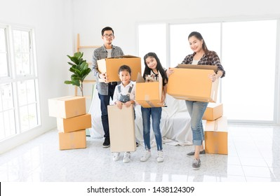 asian family holding big paper box together, they will decorating and cleaning home, they feeling happy in family time, they move to a new residence