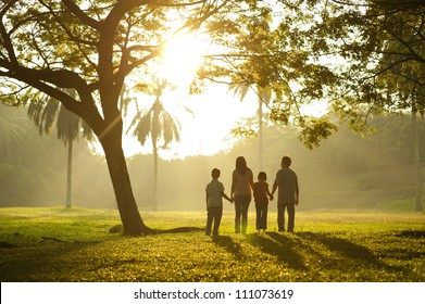 Asian family holding hands and walking towards light