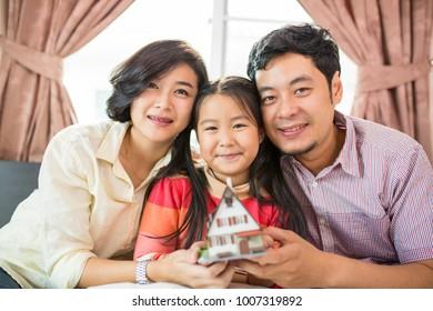 Asian family holding model house for new home in bedroom.