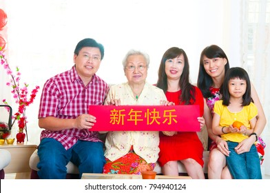 """Asian family holding red banner with chinese word """"Happy New Year"""""""