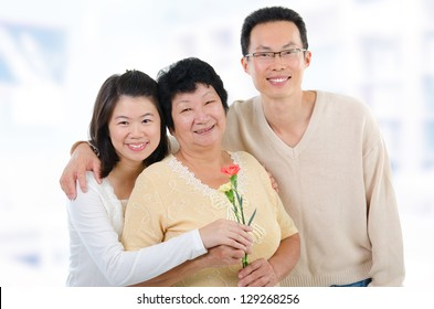 Asian family at home. Adult offspring giving carnation flowers to senior mother.
