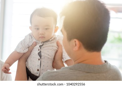 Asian family at home. Father holding child, living lifestyle indoors.