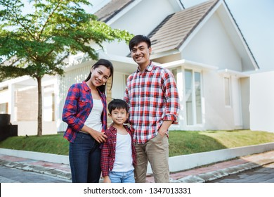 asian family with kid portrait in front of their house together in the morning