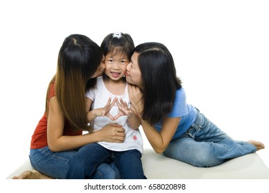 Asian family kissing little girl face on white background. Sisterly love.