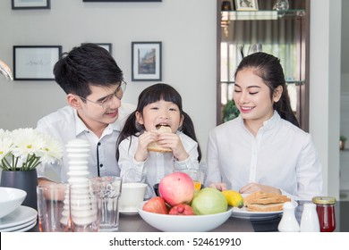 Asian Family laughing around a good meal in kitchen ,mealtime Together Asian Family have breakfast