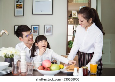 Asian Family laughing around a good meal in kitchen ,mealtime Together have breakfast.