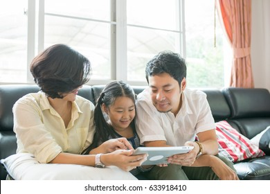 Asian family lifestyle. Father ,mother and daughter watch tablet for enjoy together in guest room.
