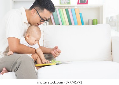 Asian family lifestyle at home. Father and child reading story book on sofa.