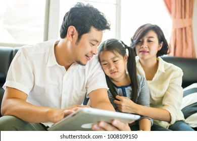 Asian family looking tablet for teach children home work