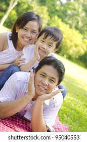 Asian family lying outdoors smiling