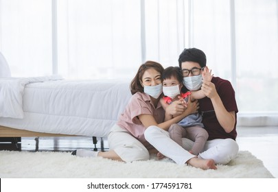 Asian Family in medical masks on the face looks at the camera while standing in the living room at home to prevent PM2.5 dust, smog, air pollution and COVID-19. Healthcare concept.