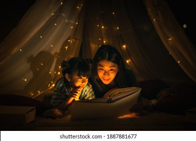 Asian family mom and girl happy at night time in bedroom at home before bed time reading fantasy bedtime story book together in kid tent with dim yellow light