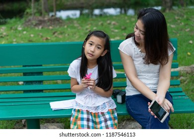 Asian Family Mother and Daughter child girl sit in the park