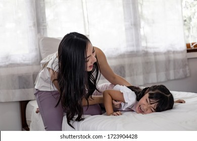 Asian family, mother and the daughter playing in the bed in the bedroom happily and joyfully. Happy loving family concept. Mother and her daughter child girl playing together.