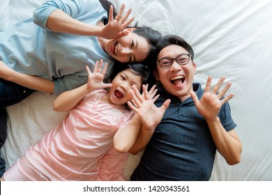 Asian Family mother father and daughter making a fun sleep play in living room home background.