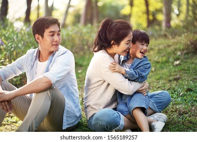 asian family mother father and son sitting on grass relaxing having fun outdoors in park