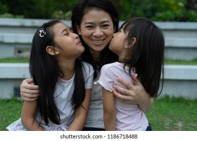 Asian Family Mother kiss Daughter child girl sit in the park