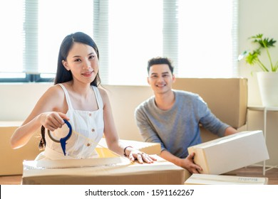 Asian family moving house, young cute woman using tape packing box while man carrying boxes. Wife and husband looking at camera and smile with happy face. Home moving and delivery, girl sitting front.