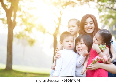 Asian family at nature park, parents and children, outdoor in morning with sun flare.