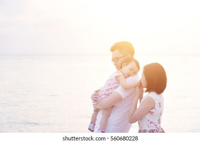 Asian family outdoor portrait, enjoying holiday together on beach side in sunset during vacations.