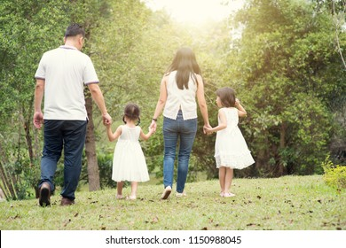 Asian family outdoors. Parents and children holding hands and walking at garden park. Rear view.