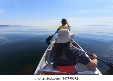 Asian family paddles in the Lake Superior Provincial Park in a calm summer afternoon