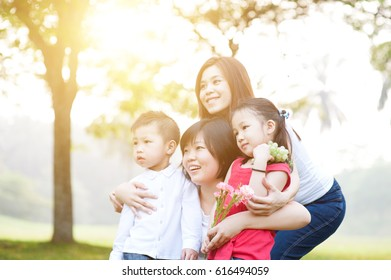 Asian family at park, parents and children, outdoor in morning with sun flare.