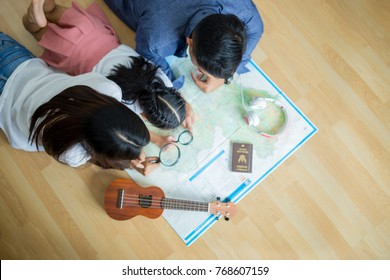 asian family is planning a travel trip.They're looking at a world map