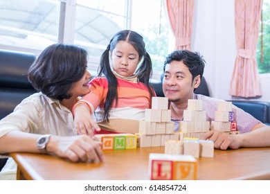 Asian family play cube wood for build words together in guest room.