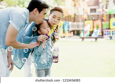 Asian family is playing balloon bubbles in the park, which is ideal for long weekend vacations. Taking care of family makes children feel the love of parenting. Family health insurance is a good plan.