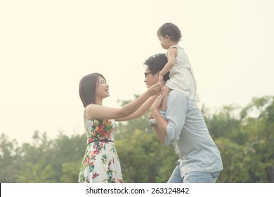 asian family playing and enjoying quality time outdoor , vintage tone
