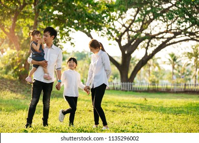 Asian family portrait with happy people smiling at the park ,Lifestyle and Holiday Concept.
