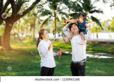 Asian family portrait with happy people smiling at the park ,Lifestyle and Holiday Concept