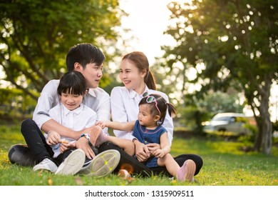 Asian family portrait with happy people smiling at the park sun set,Lifestyle and Holiday Concept.